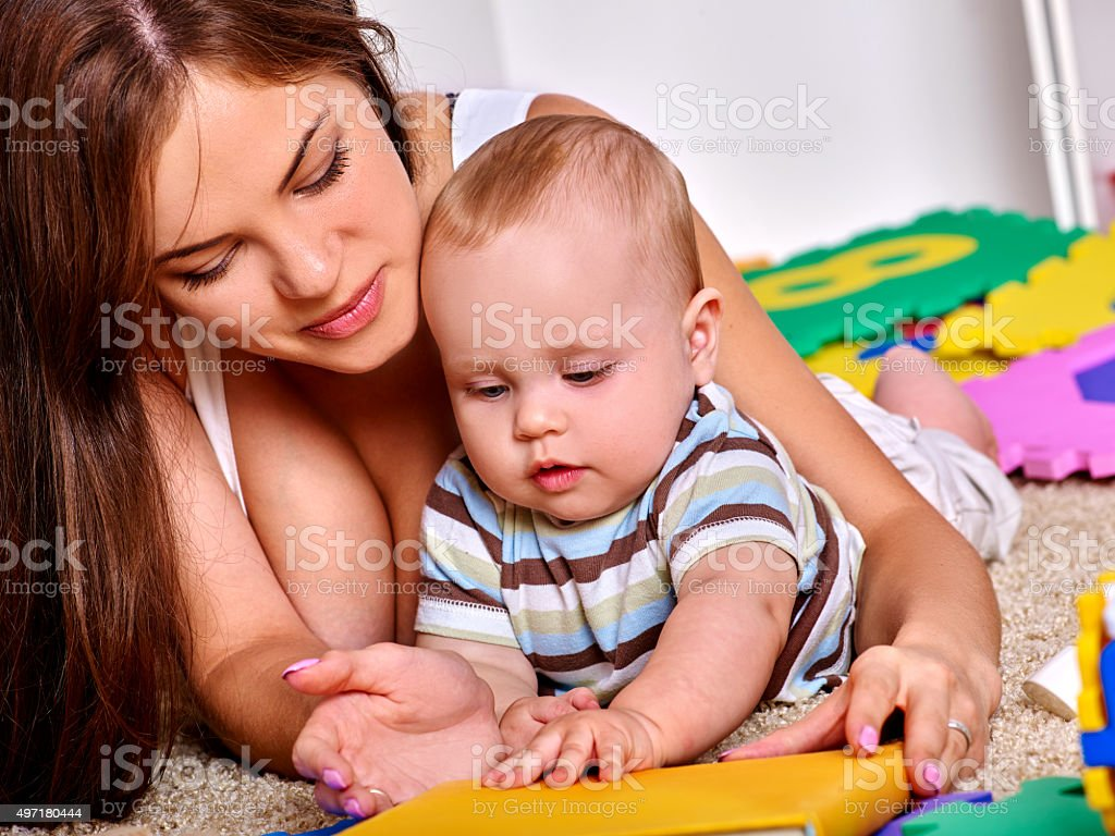 Kid baby boy plying with puzzle toy on floor stock photo