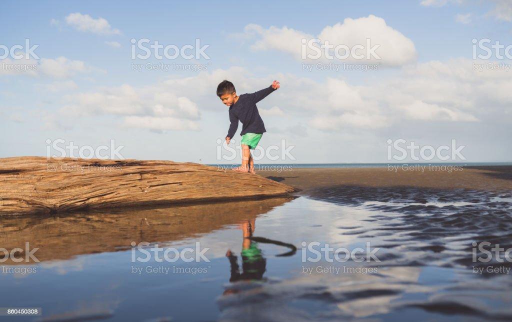 Kid balancing up himself on log at beach. stock photo