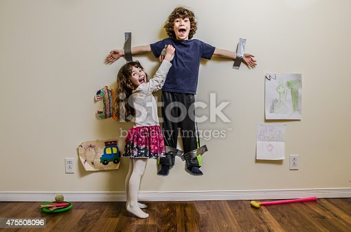 A little girl hung her brother on the wall using duct tape