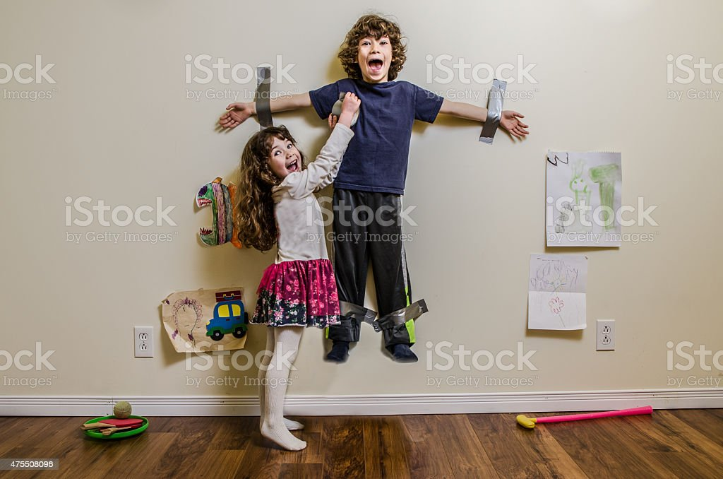 Kid being duct taped on wall by his sister stock photo