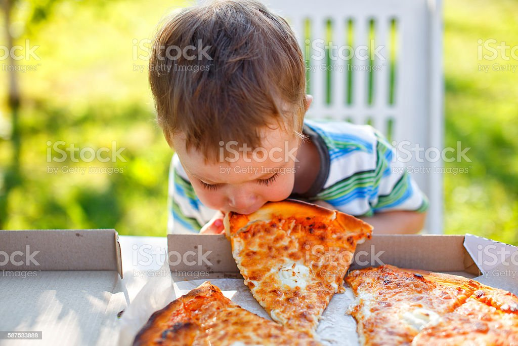 kid biting a slice of pizza stock photo