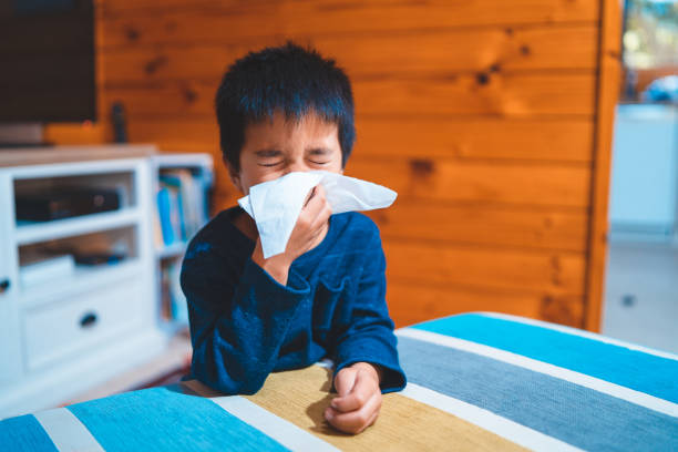 Kid Blowing Nose with Tissue. stock photo