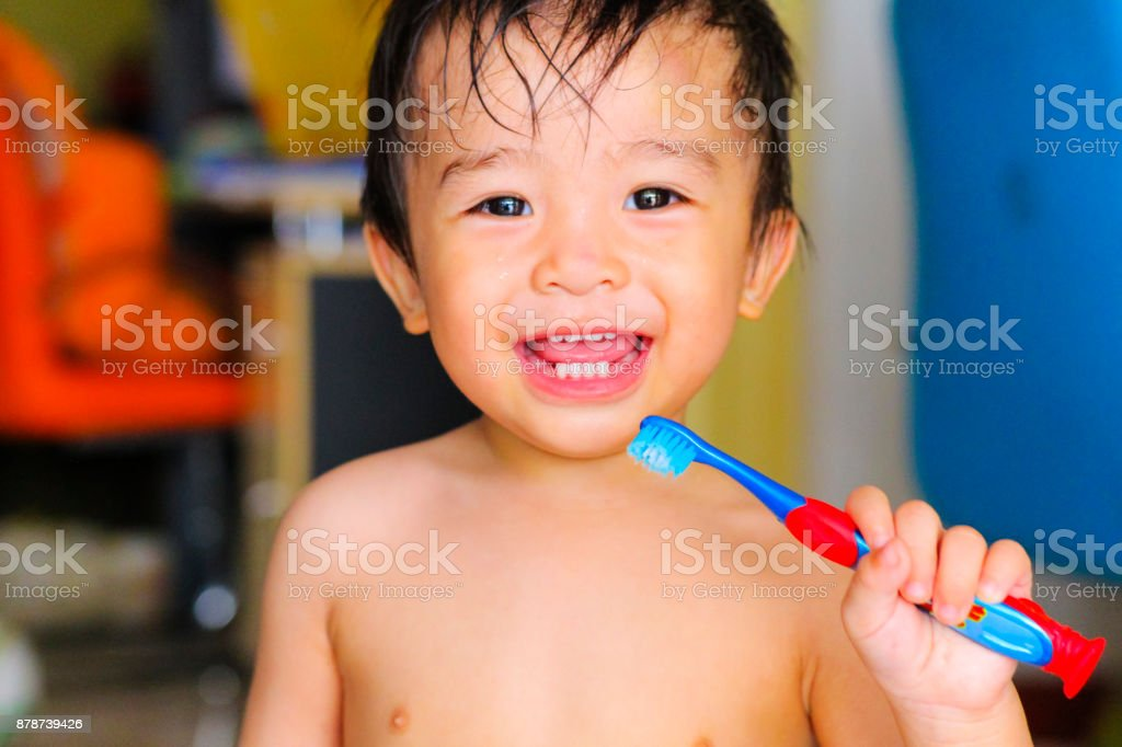 kid boy brushing teeth and smiling stock photo