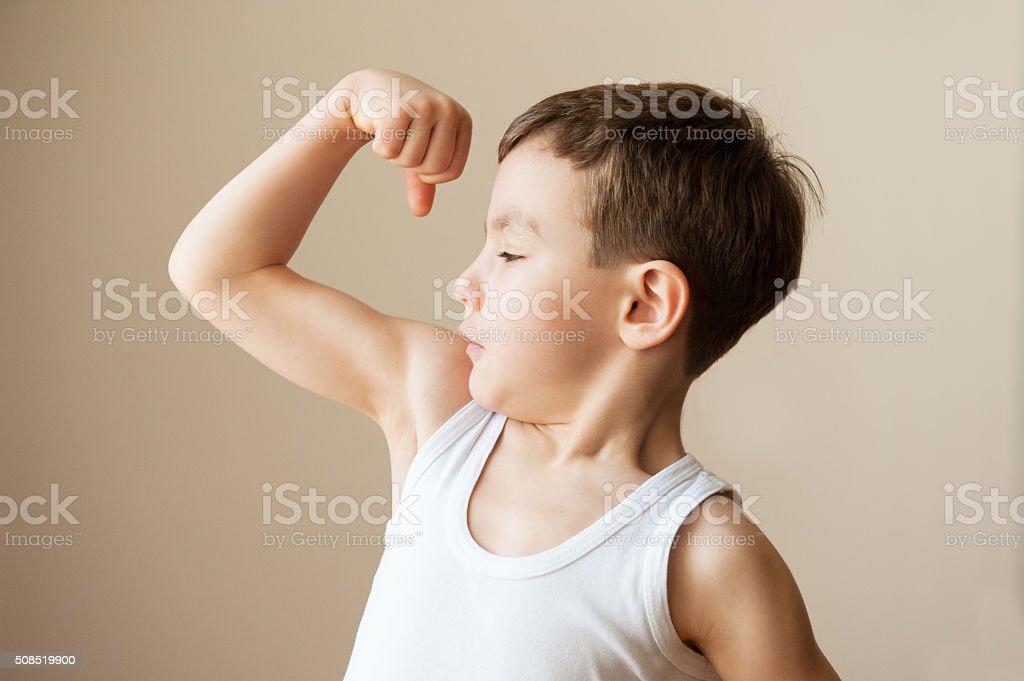 Criança menino criança mostrando os músculos punho de musculação - foto de acervo