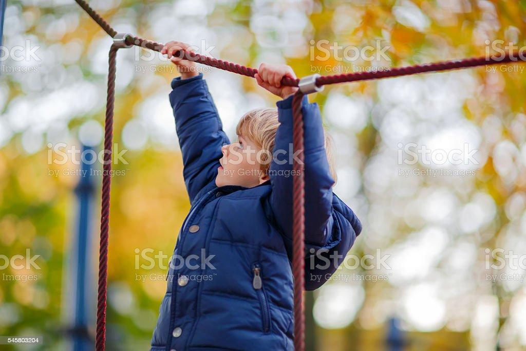 kid boy climbing on outdoor playground on autumn day stock photo