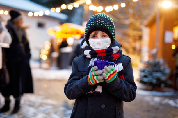 Kid boy drinking hot children punch on German Christmas market. Happy child with medical mask . People with masks as protection against corona virus. Covid pandemic time in Europe and in the world. stock photo