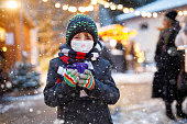 istock Kid boy drinking hot children punch on German Christmas market. Happy child with medical mask . People with masks as protection against corona virus. Covid pandemic time in Europe and in the world. 1284706563