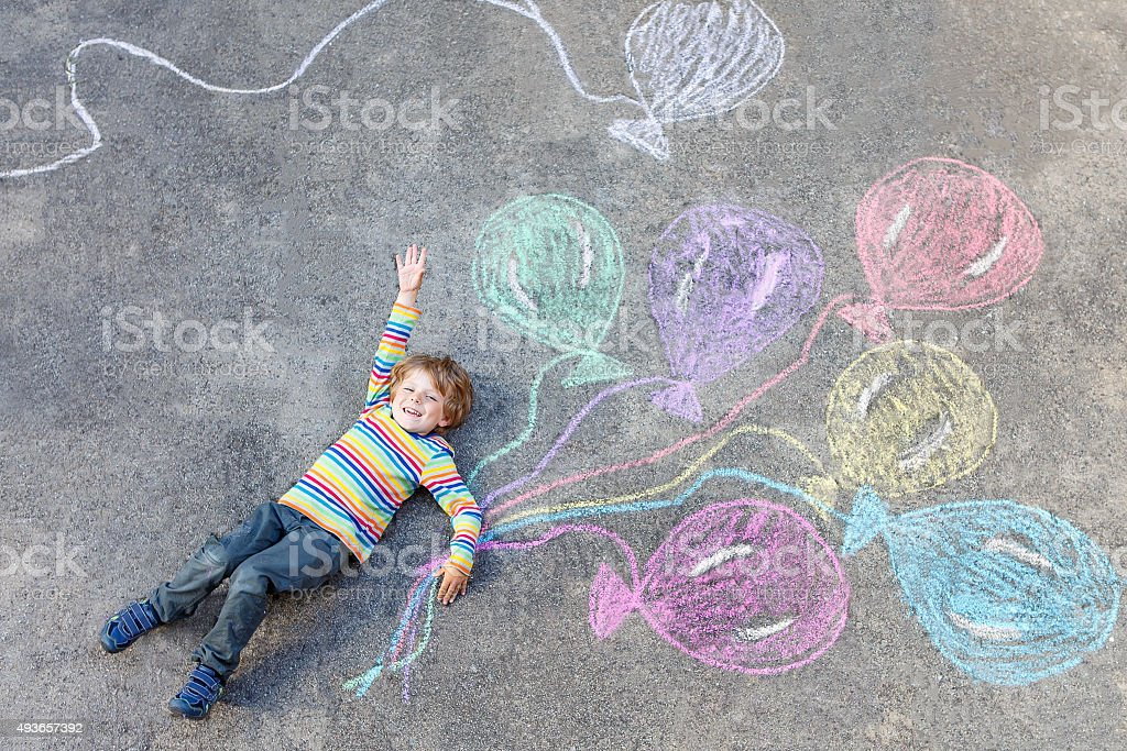 Kid boy having fun with colorful balloons drawing with chalks stock photo