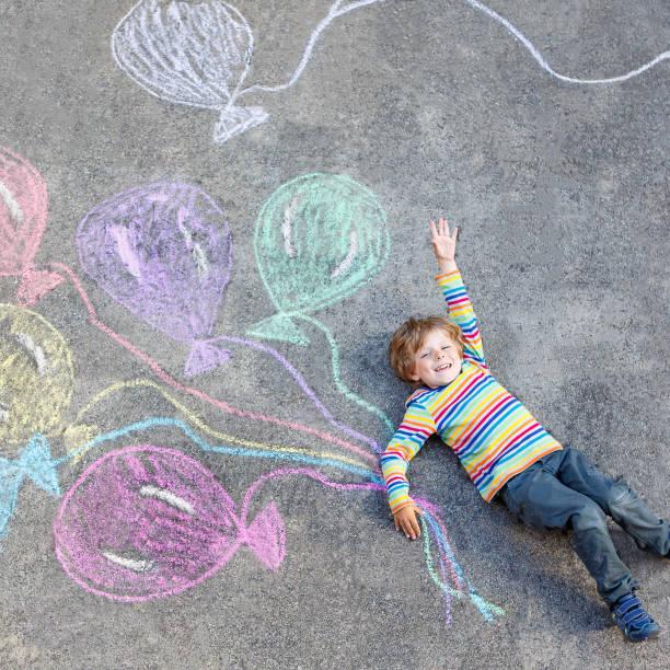 kind junge spaß mit bunten ballons zeichnung mit chalks - vorschulgeburtstag stock-fotos und bilder