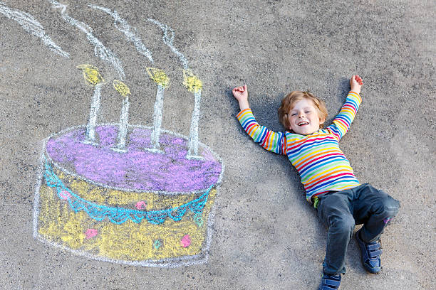 kid boy having fun with colorful birthday cake chalks - geburtstagstorten bilder stock-fotos und bilder