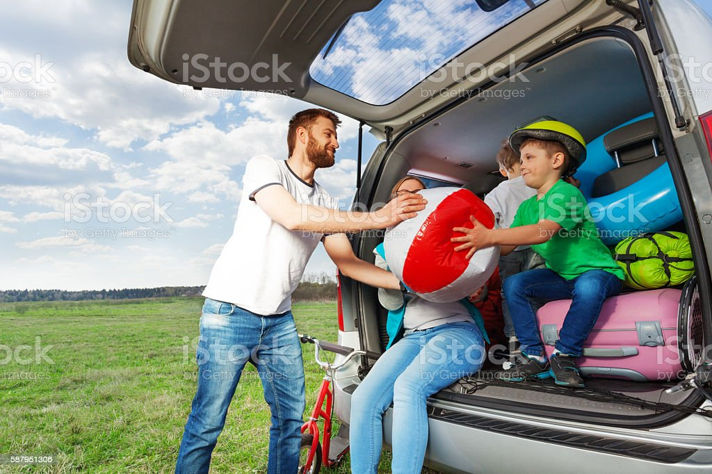Kid boy helping his father to load their car boot stock photo