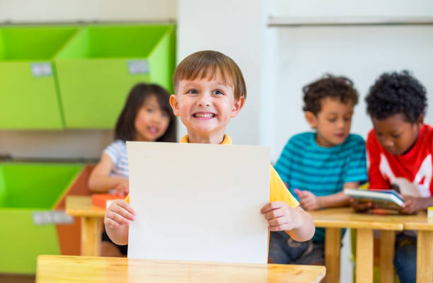Kid boy holding blank paper with back to school word with diversity friends and teacher at background,Kindergarten school,mock up chalkboard for adding text stock photo