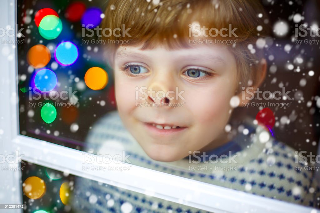 Kid boy near window and looking outdoors on Christmas stock photo