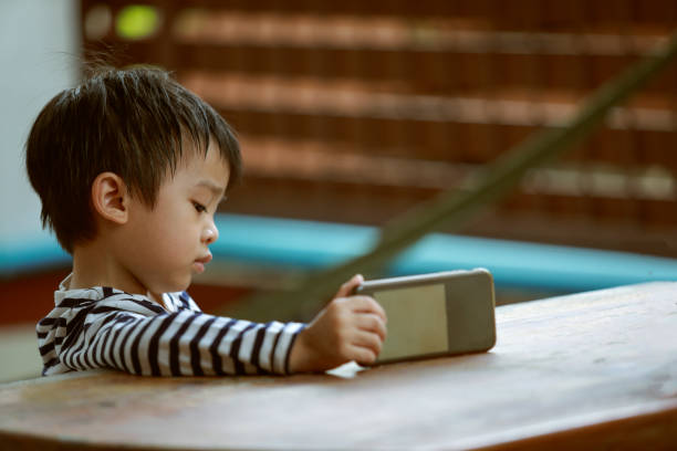 kid boy playing and looking smartphone - asian with phone house background stock photos and pictures