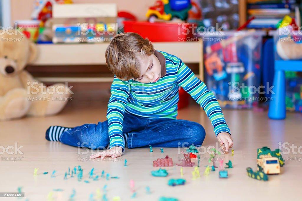 Kind Junge spielt mit Spielzeug im Kindergarten Soldaten im Innenbereich – Foto