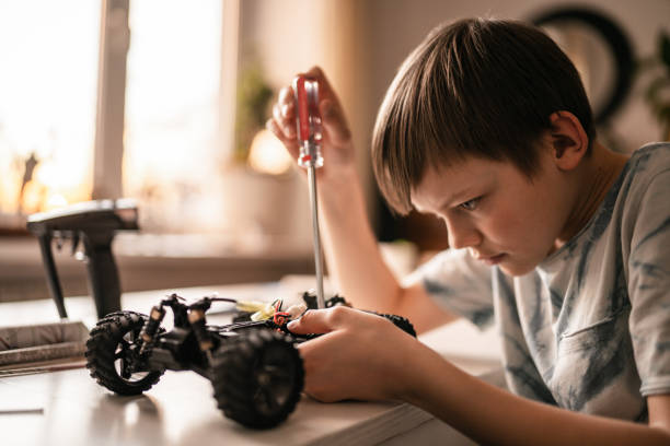 Kid boy repairs a remote controlled car  toy stock photo
