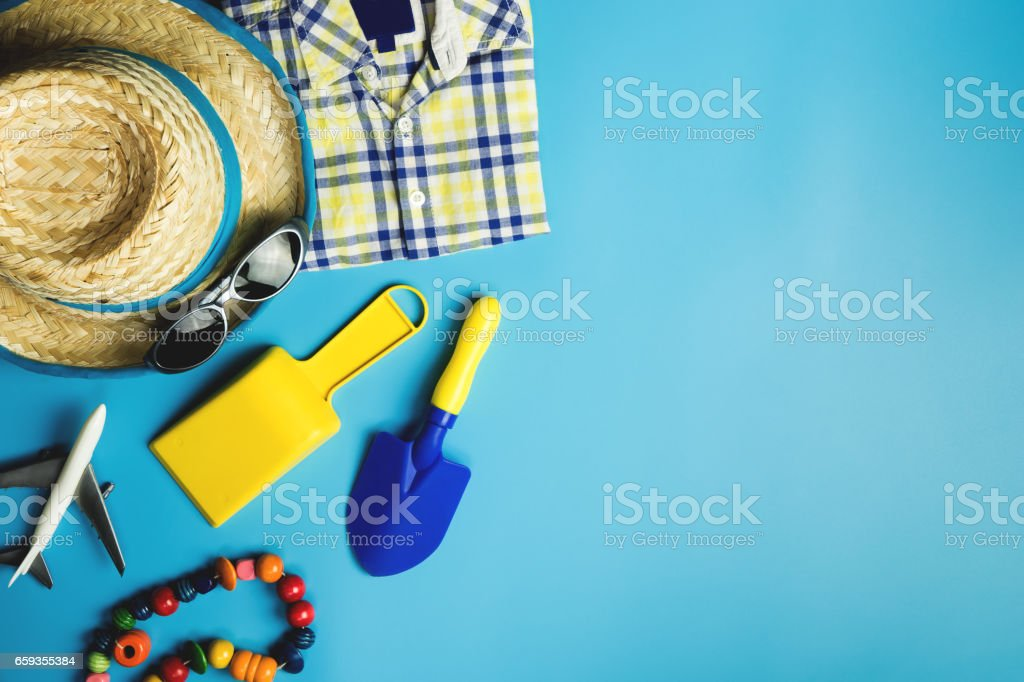 Kid boy travel accessories and toys on blue copy space stock photo