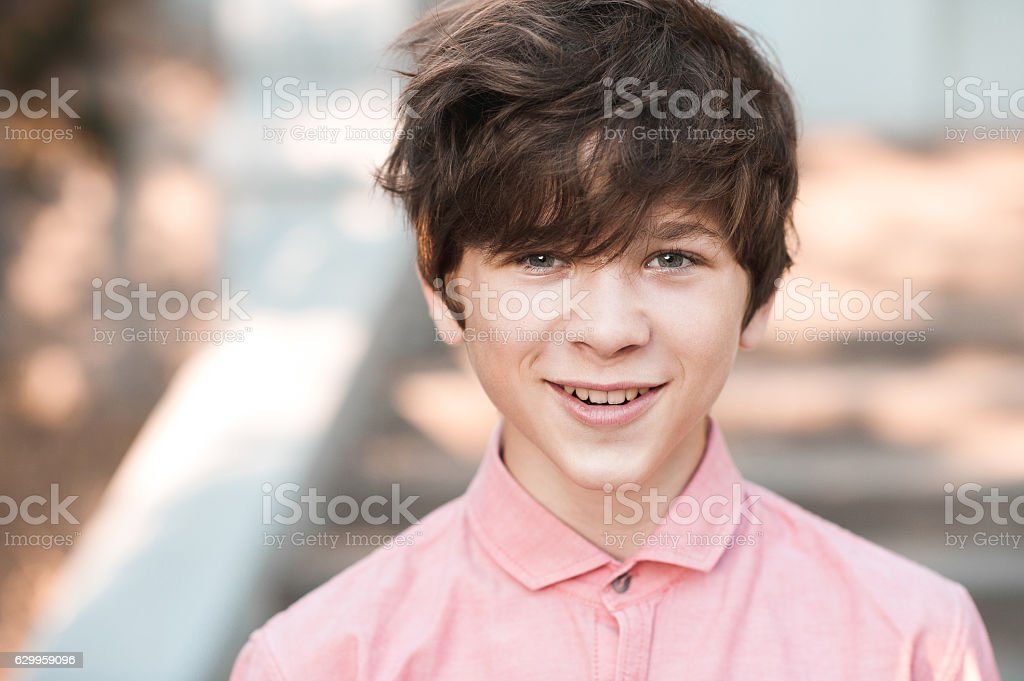 Kid boy with messy hair outdoors stock photo