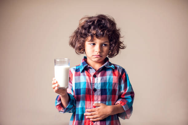 kid jongen met maagpijn met een glas melk. zuivel intolerante persoon. kinderen, gezondheidszorg concept. - allergie stockfoto's en -beelden