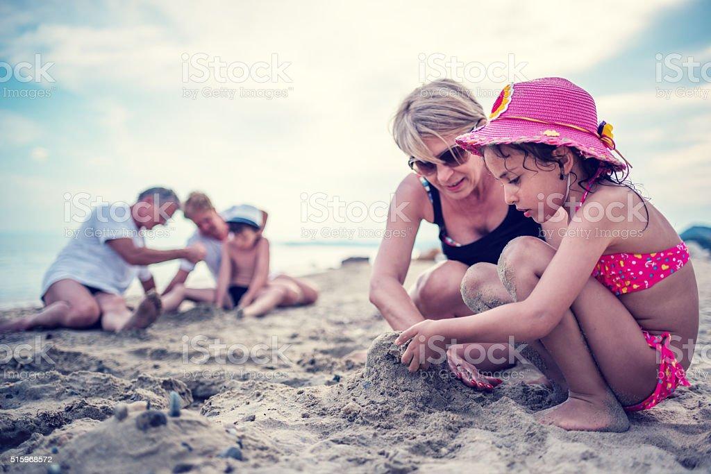 Kinder Sandburgen mit Großmutter am Strand – Foto