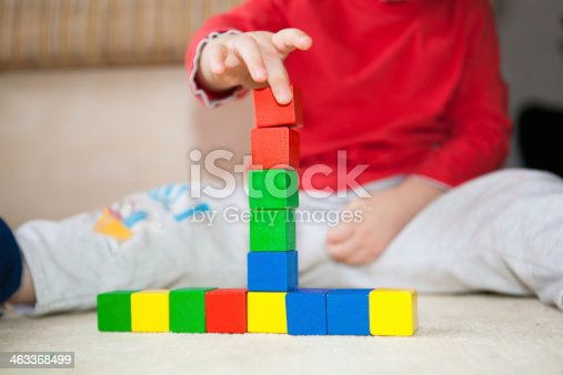 657779378 istock photo Kid building tower with cubes. 463368499