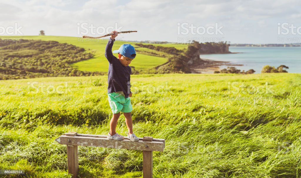 Kid climbed on a sign with scenic view in background. stock photo