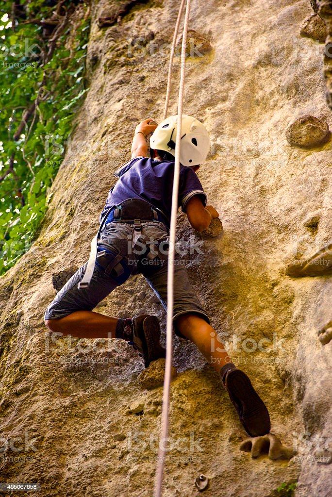 Kind Klettern eine Felswand gesehen von unten – Foto