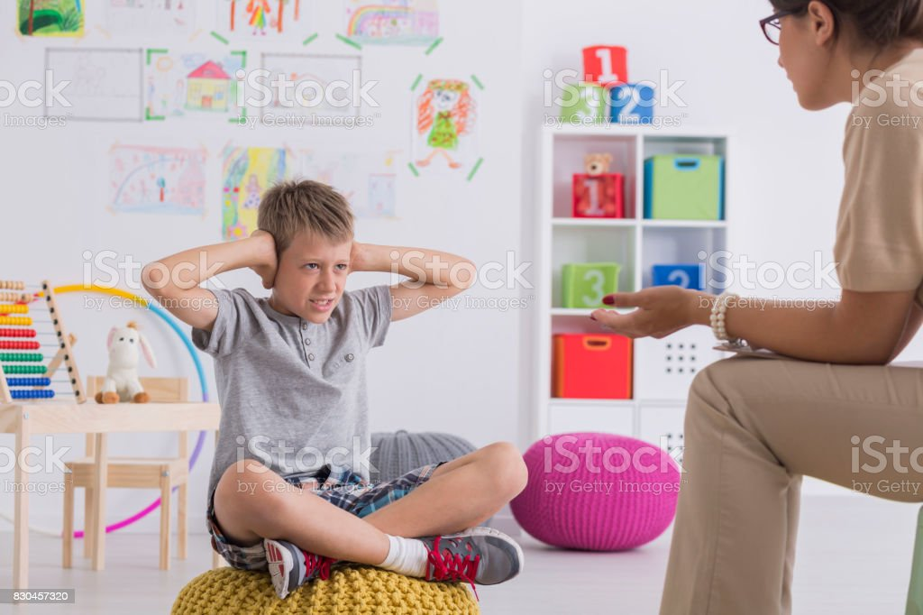 Kid covering his ears during therapy – zdjęcie