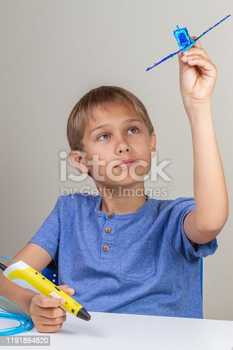 899701486 istock photo Kid creating with 3d pen and enjoy his new blue plane 1191894820