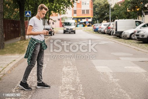 Schoolboy with mobile phone on pedestrian crossing going home