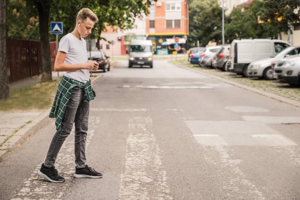 kid oversteken van de straat bij een voetgangers kruising en luisteren naar muziek op zijn mobiele telefoon - voetganger stockfoto's en -beelden