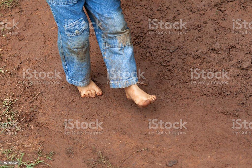 Kid dirty feet on muddy ground stock photo