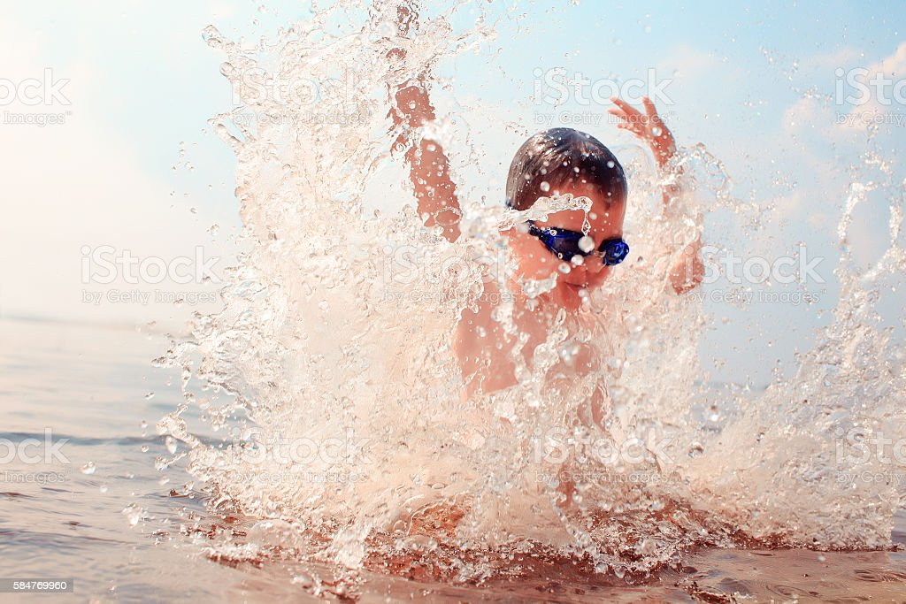 kid dives into the water stock photo