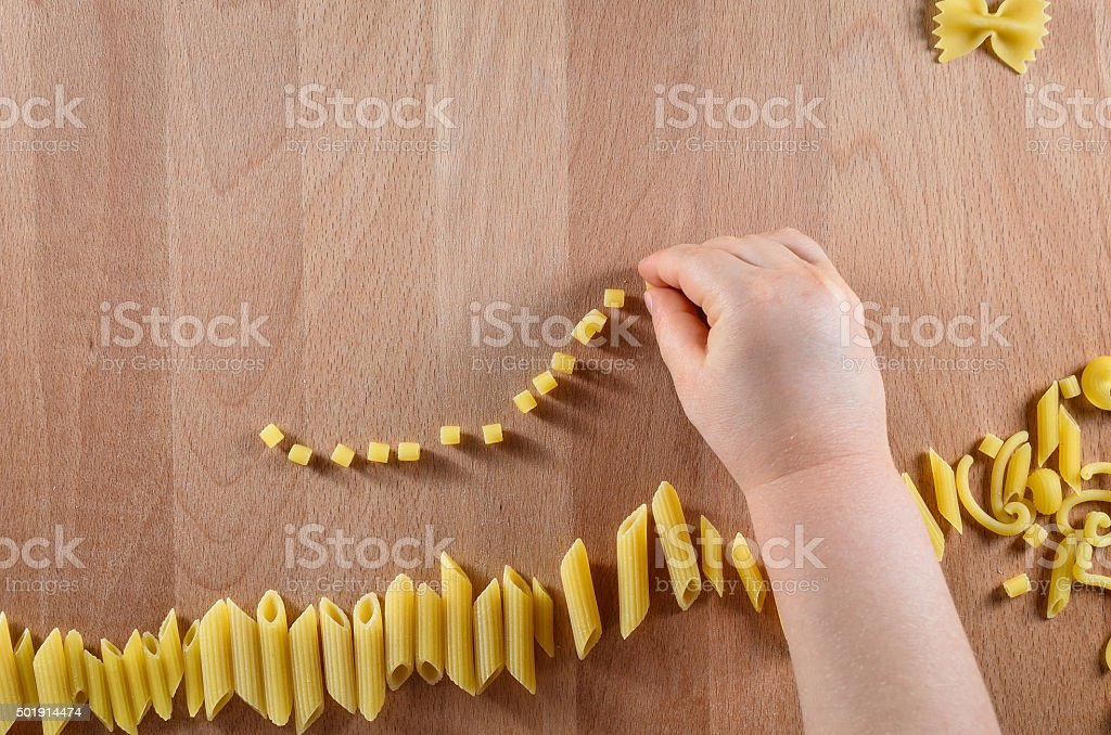 kid doing activity in school with noodles stock photo