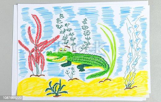 istock Kid doodle of cute crocodile underwater on sand bottom with seaweeds. 1087665220
