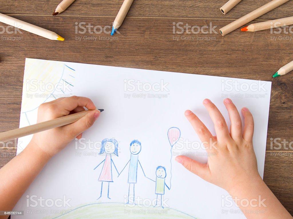 Kid drawing a happy family stock photo