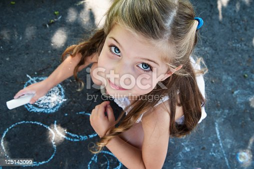 istock Kid drawing on the pavement of a driveway. 125143099