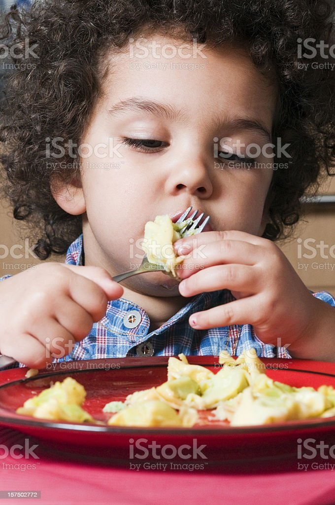 Kid eating pasta on her own stock photo