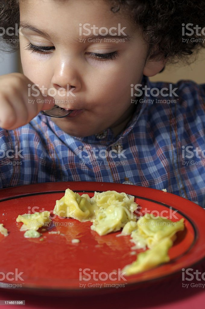 Kid eating pasta on her own. stock photo