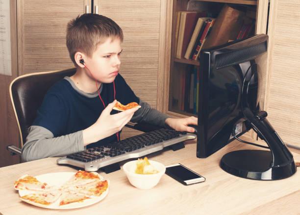 Kind, Pizza essen und Surfen im Internet oder Watshing video auf PS. Boy Kopfhörer Fastfood mit Computer in seinem Zimmer. – Foto