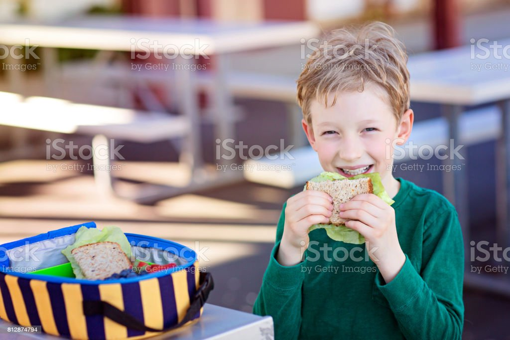 kid eating school lunch stock photo