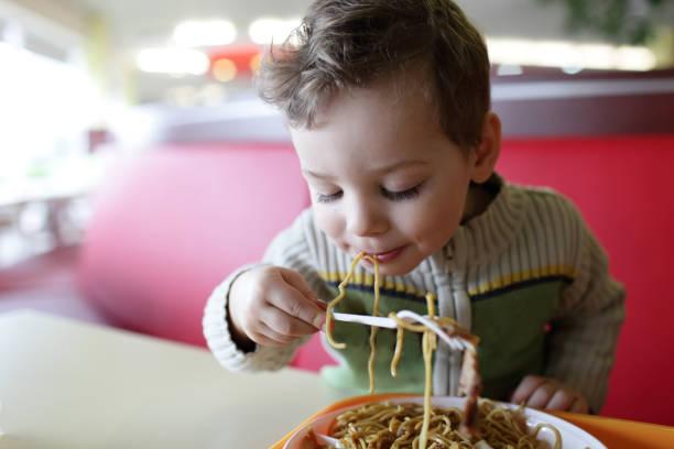 Niños comiendo espaguetis - foto de stock