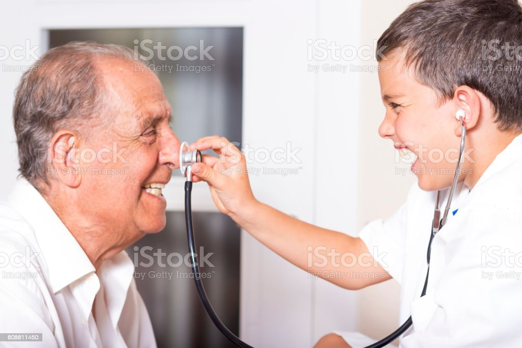 Kid examines his grandfather using stethoscope stock photo