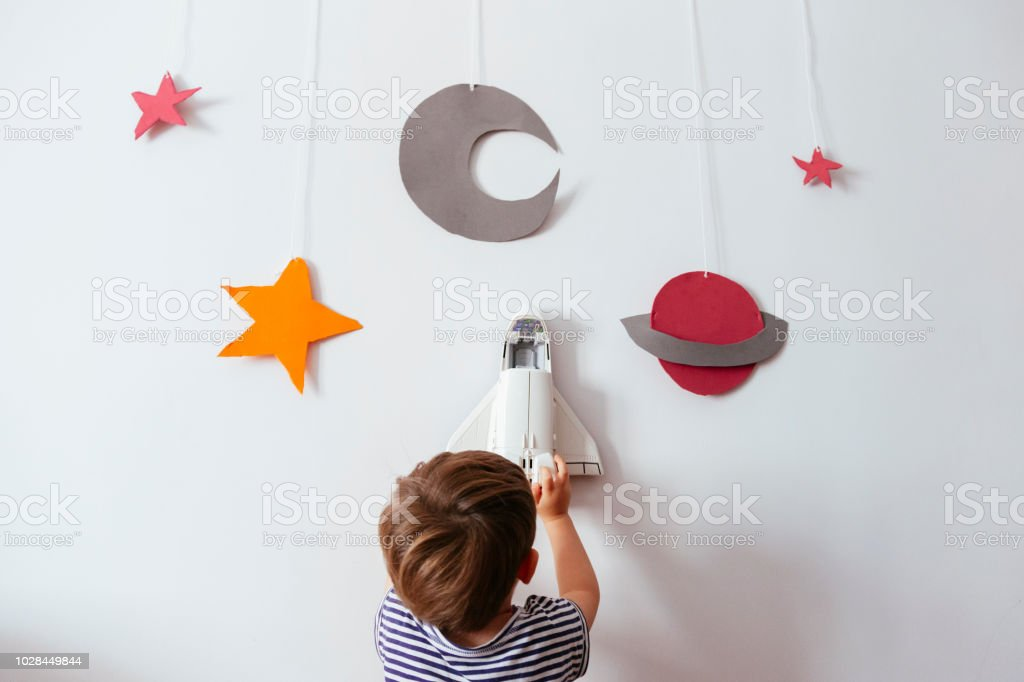 kid flying a space ship between a galaxy stock photo