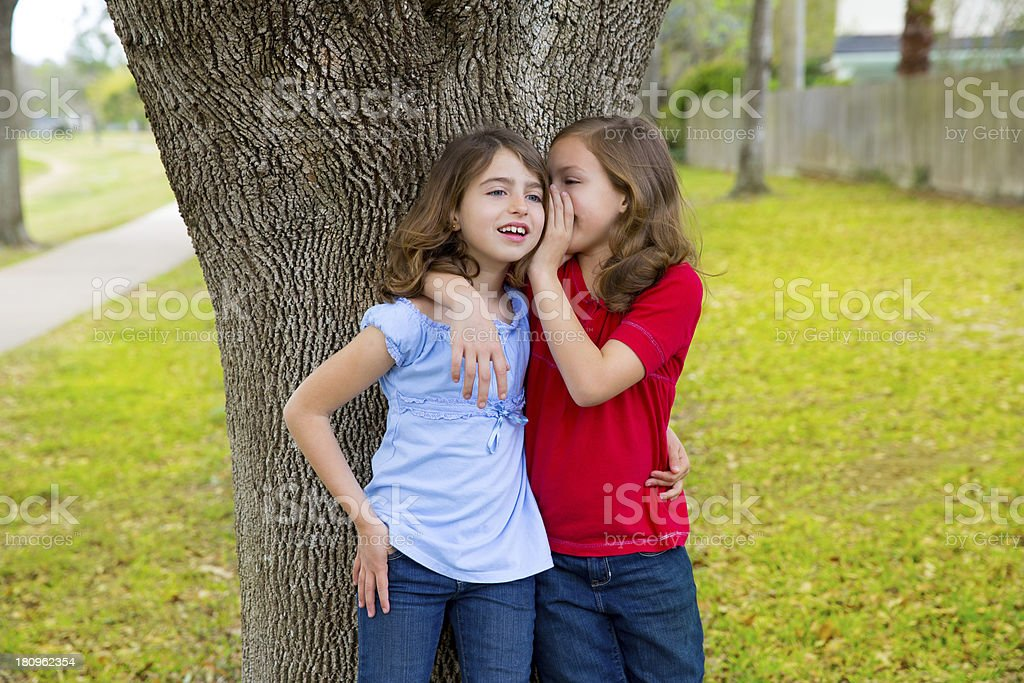 kid friend girls whispering ear playing in a park tree stock photo