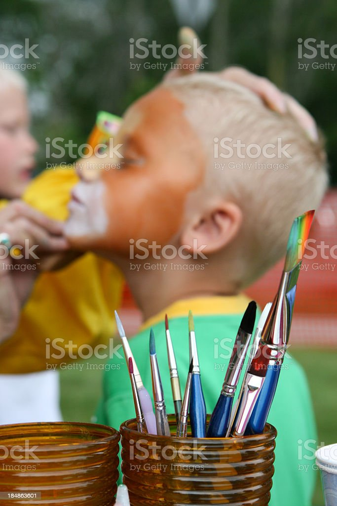 Kid getting face painted royalty-free stock photo