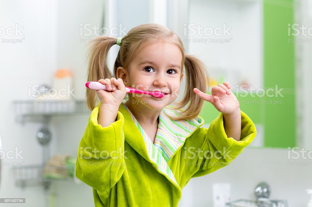 kid girl brushing teeth in bathroom stock photo