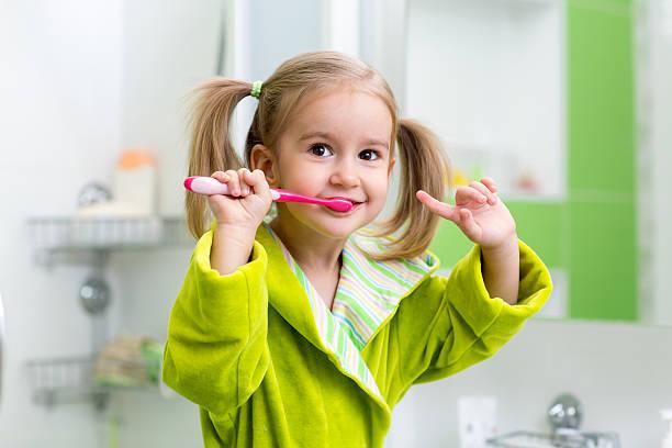 kid girl brushing teeth in bathroom stock photo
