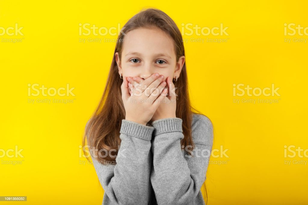 Kid girl covers her mouth with surprise, children\'s secret. Portrait...