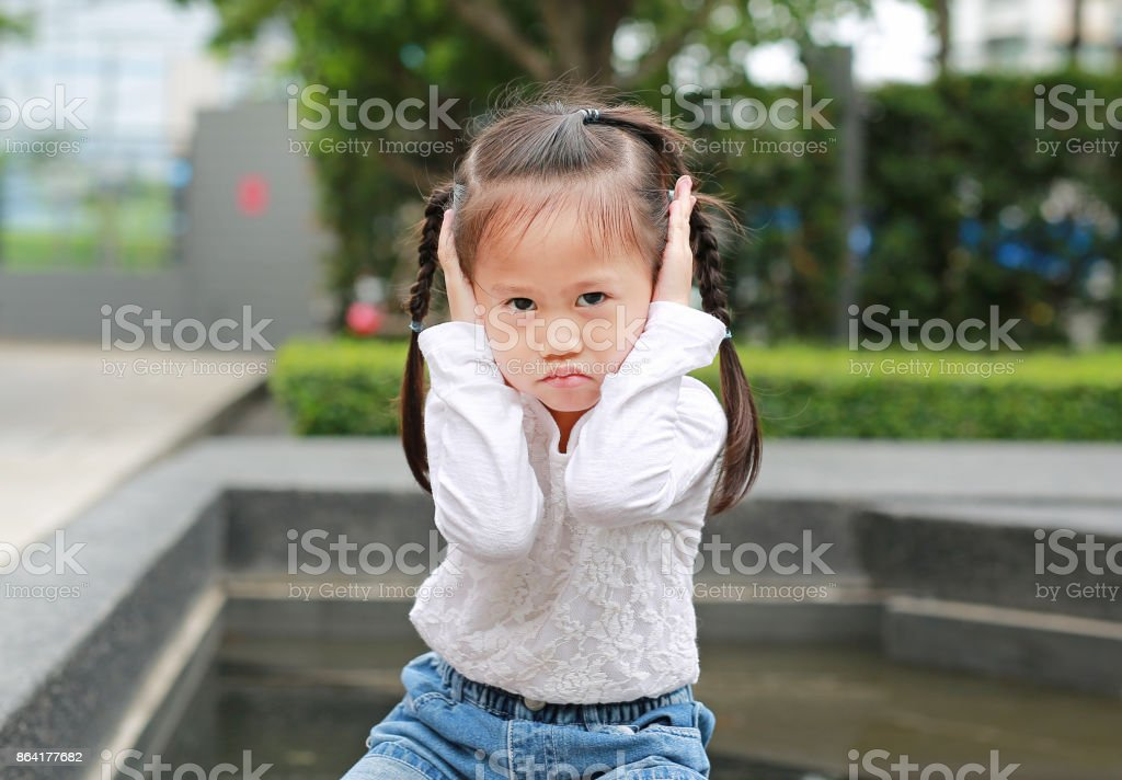 Kid girl holding her hands covers ears not to hear. stock photo